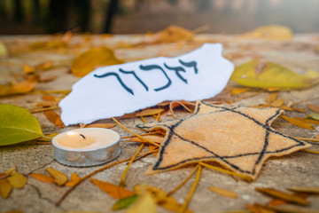 "Hebrew inscription ""remember"", cande and Star of David on autumn leaves in the park"