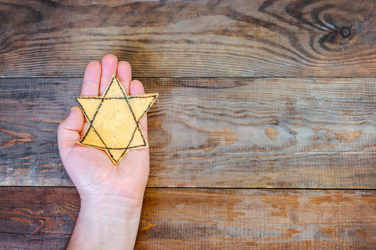 Male hand and star of David on a wooden board background. Holocaust Remembrance Day