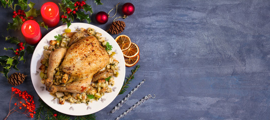 Roasted chicken with apple and bread stuffing. Christmas decorations. Dish for Christmas Eve. New Year food menu. Layout, flat lay, view from above, copy space