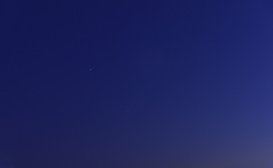 Clear navy blue twilight sky with several stars at sunset