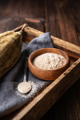 Poster Baobab Organic baobab powder in a wooden bowl, healthy sport nutrition rich in vitamins and minerals