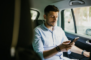 Young man texting with client on phone while trip on backseat of office car