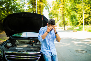 Young man on the road having problem with a car. Broken down car on the road. Traveling problem in road.