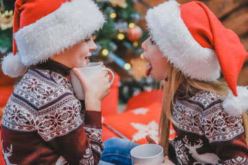 Cropped photo of funny brother and sister drinking hot chocolate and making fun in a cozy living room on Christmas eve.