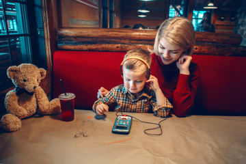 Portrait of young blonde Caucasian mother with toddler boy son sitting in cafe restaurant and playing electronic digital gadget device toy. Child listening to music with earphones.