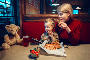 Caucasian family mother with toddler boy son eating food dinner in cafe restaurant and playing electronic digital gadget device toy. Children kids adult addiction to cell mobile phones.