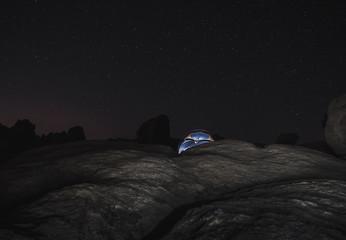 tent lit up under starry night