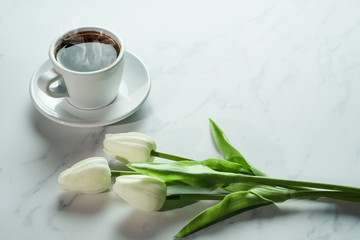 coffee background of a cup of hot black coffee with bunch of white tulip on white marble background