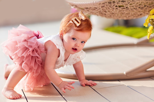 lovely little baby girl crawling on the decking at the patio