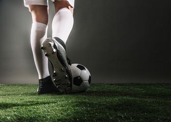 man kicks a soccer ball isolated dark background