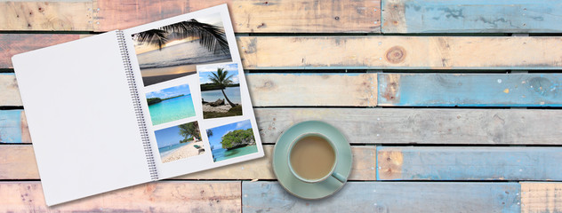 Banner Photobook Album with Travel Photo on Wooden Floor Table with Coffee or Tea in Cup