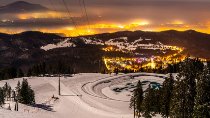 Poiana Brasov, Romania, The hearth of Transylvania, one of the most picturesque Europe`s ski resort.  Wooden chalets and spectacular ski slopes in the Carpathians. View at night.