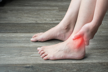 Closeup of woman hands holding and touching her ankle, suffering from ankle pain. Ankle pain may be caused by an injury, like a sprain, or by a medical condition, such as arthritis.
