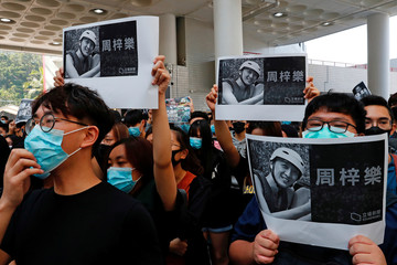 Students hold images of Chow Tsz-Lok, 22, a university student who fell during protests at the weekend and died early on Friday morning, during a ceremony to pay tribute to him at the Hong Kong University of Science and Technology