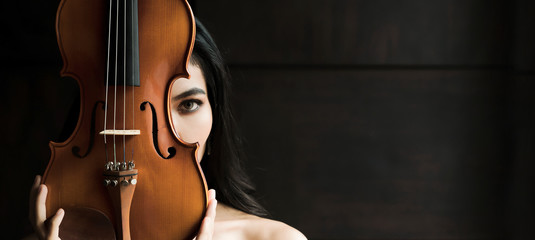 Close up portrait of young asian woman playing violin vintage style with copy space. Musician orchestra performer artist lifestyle concept panoramic banner