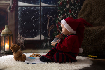Sweet toddler boy, reading book at home at night on Christmas