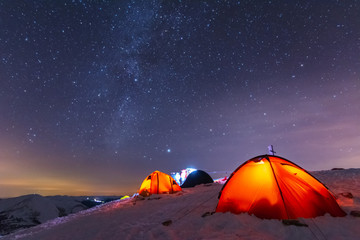 Great bright campsite with colorful tourist tents, on top in the Ukrainian Carpathian Mountains, at night with views of the stars and the Milky Way