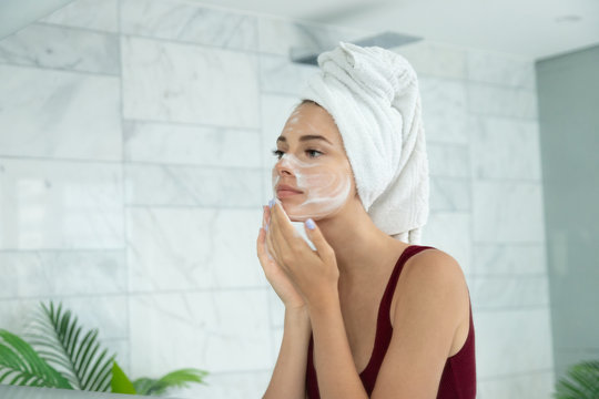 Beautiful  woman applying facial  foam. Pretty girl standing front of mirror in bathroom side view. Daily skincare and hygiene. Cleansing, moisturizing and protection skin
