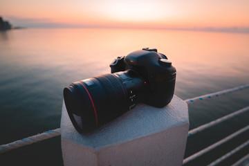 Dslr digital camera with lens close up at sea pier at sunset
