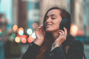 Young happy stylish trendy casual hipster woman teenager listening to music on a wireless headphone while walking around the city. Music lover enjoying music