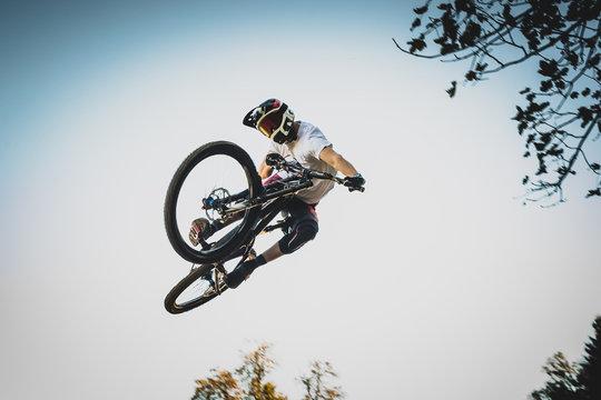 Mountain biker jumping over a dirt jump.