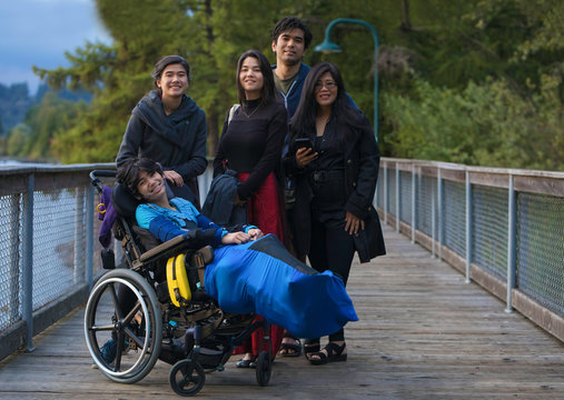 Asian mother with adult children and disabled  son in wheelchair