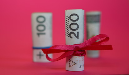 Rolled banknotes of 200 Polish zloty tied with red ribbon concept of economical / financial gift, behind two rolls of 100 zloty in soft focus, isolated on pink background close up