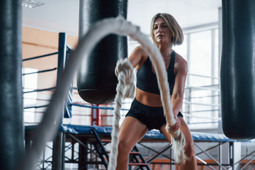 Session with battle ropes. Blonde sport woman have exercise in the gym. Strong female Wall mural