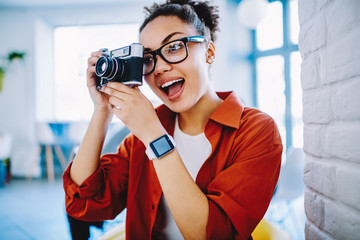 Surprised female amateur photographer in optical spectacles making photo via vintage camera, dark skinned amazed woman with expression on face taking pictures using old fashioned equipment indoors