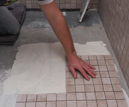 Renovation work performed by the master in the shower room for lining the walls and floors with decorative mosaics using a special tool and white glue for ceramic tiles.