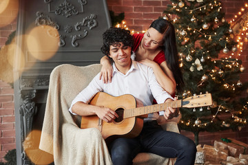 Curly haired attractive guy sitting on the chair with acoustic guitar with Christmas tree behind. Girlfriend in white dress is hugging her boyfriend