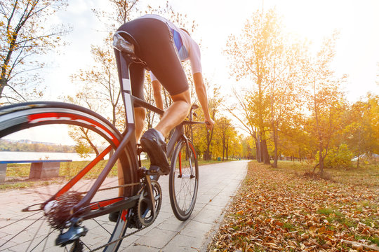 Young male triathlete riding bike in autumn park