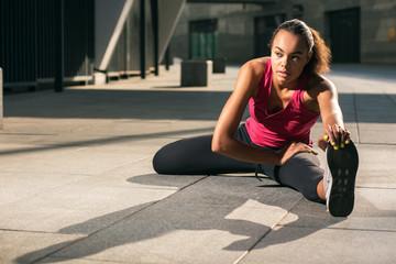 Thoughtful professional sportswoman pulling leg stock photo