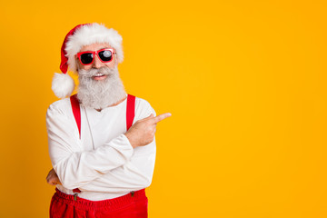 2020 christmas resolution discounts. Funny funky grey hair santa claus in red hat point index finger indicate x-mas time sales isolated over yellow color background