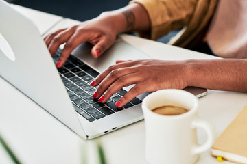 Woman having coffee and using laptop in office
