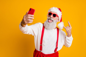 X-mas party hard. Portrait of funny crazy santa claus in red hat take selfie smart phone christmas blogger show horns grimace tongue out wear shirt suspenders isolated yellow color background