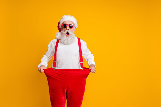 Portrait of crazy funky white bearded grandfather in santa claus hat hold big size trousers lose weight belly x-mas time show dieting effect isolated yellow color background