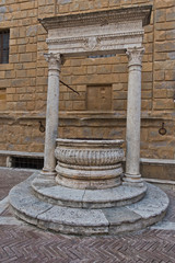 Well in front of a church wall at small square in Pienza , Siena province, Tuscany, Italy