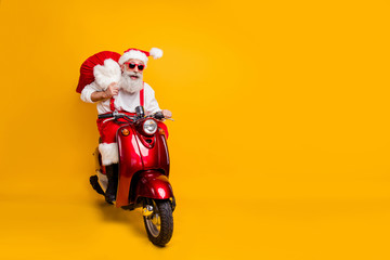 Full body photo of crazy funny santa claus in red hat drive hurry fast motor cycle hold sack christmas x-mas preparation ride north-pole wear shirt suspenders isolated yellow color background
