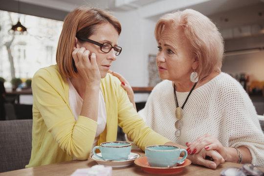 Senior woman comforting her upset adult daughter. Depressed mature woman meeting her elderly mother