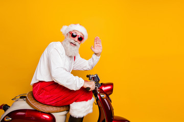 Photo of stylish santa grandpa riding x-mas party retro bike waving arm greeting gesture wear trendy sun specs red trousers cap shirt boots isolated yellow color background