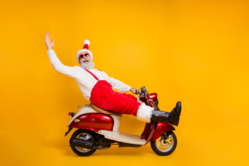 Full body photo of funny white hair santa in festive mood riding x-mas theme party by bike wear stylish sun specs trousers cap shirt boots isolated yellow color background