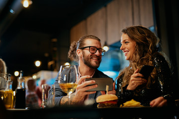 Handsome caucasian hipster man taking photo of his food while sitting in restaurant. Next to him is his girlfriend holding smart phone and looking at him.