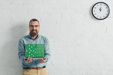 handsome and smiling businessman holding laptop with football website