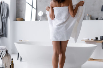 Slim Afro American lady taking off the towel