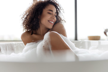 Charming Afro American woman relaxing in bathtub
