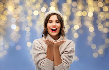 christmas, holidays and celebration concept - happy smiling young woman in knitted winter hat and...