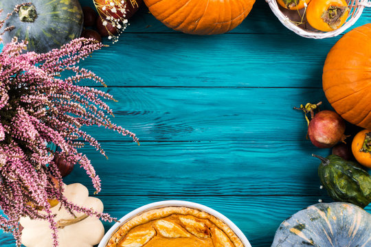 Autumn thanksgiving moody background with pumpkin pie, different pumpkins, fall fruit and flowers on green rustic wooden table. Flat lay