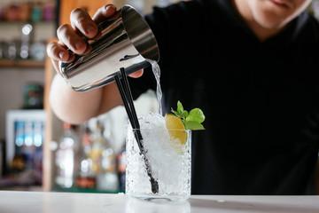Close-up of professional bartender making Caipirinha cocktail