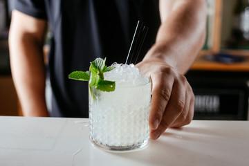 Close-up of professional bartender serving  Caipirinha cocktail